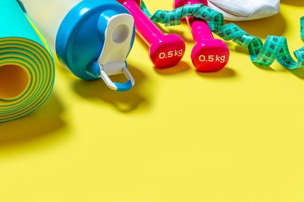 Sprzęt sportowy i fitness na żółtym tle