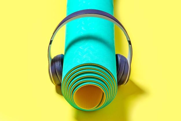 Sprzęt sportowy i fitness, słuchawki i mata do jogi słuchają muzyki