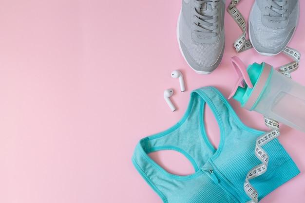 Sprzęt sportowy i odzież damska. płaskie buty sportowe, butelka, stanik, słuchawki i miarka