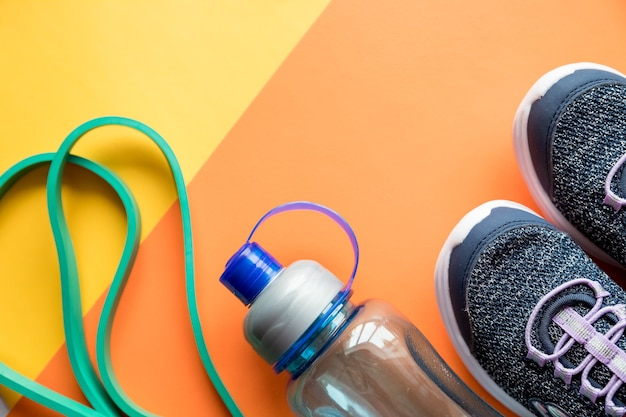Sprzęt sportowy, niebieskie trampki, skakanka i butelka wody. zdrowy styl życia, koncepcja fitness.
