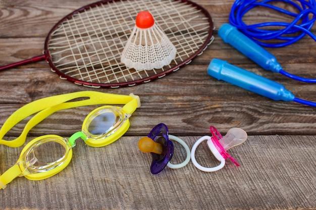 Sprzęt sportowy: ptaszek jest na rakiecie, skakanka, okulary pływackie i trampki na drewnianym tle