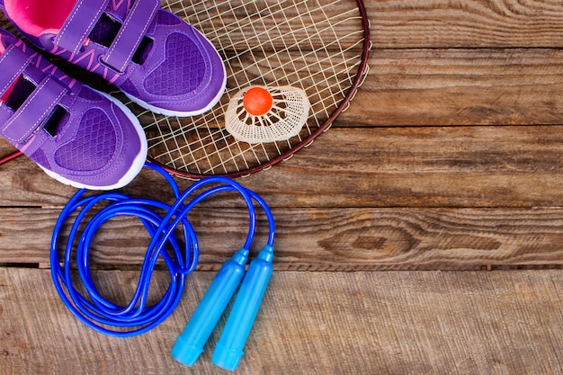 Sprzęt sportowy: ptaszyna jest na rakiecie, skakanka, okulary pływackie i trampki na drewnianym tle