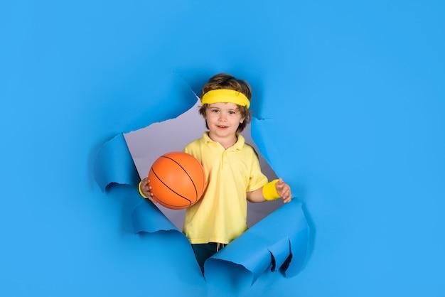 Sprzęt sportowy szczęśliwe dziecko chłopiec trzyma piłkę pokazuje kciuk w górę ciesz się grą sportową zajęcia dla dzieci słodki chłopak