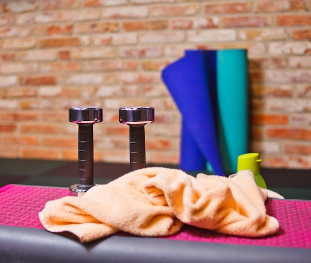 Sprzęt treningowy. metalowe hantle, ręcznik, mata, butelka wody