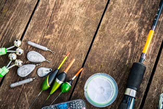 Sprzęt wędkarski na drewnianym stole. pływaki, obciążniki, żyłka, haczyki na drewnianym tle