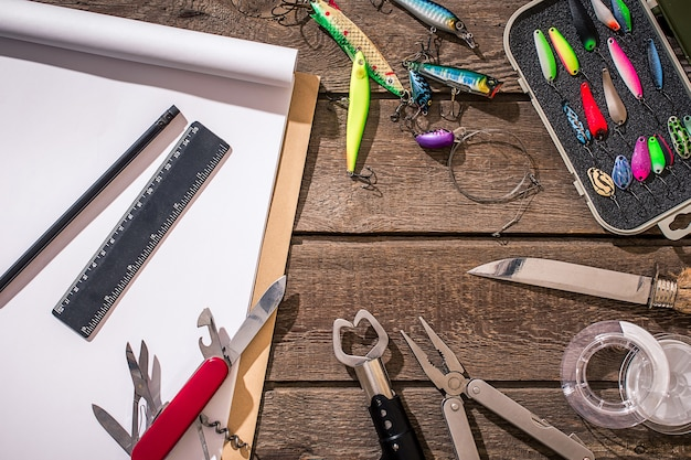 Sprzęt wędkarski - spinning wędkarski, żyłka, haczyki i przynęty na podłoże drewniane. widok z góry. skopiuj miejsce. martwa natura