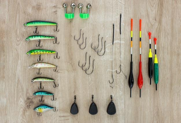 Sprzęt wędkarski wędkarstwo spławik przynęty ciężarki i dzwonki na drewnianym tle koncepcja połowów
