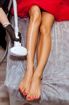 Sprzętowa procedura usuwania włosów na ciele dziewczyny kosmetyczka wykonuje depilację laserową na nodze