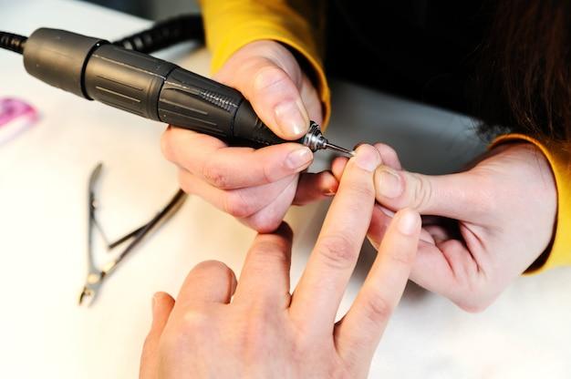 Sprzętowy manicure w salonie kosmetycznym.