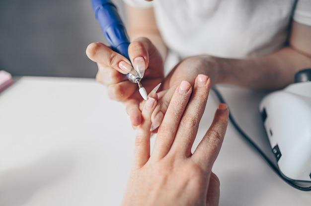 Sprzętowy proces profesjonalnego manicure, czyszczenie paznokci frezem. zamyka w górę żeńskich ręk w piękno salonie. leczenie paznokci paznokci, proces produkcji. wiertarka elektryczna do paznokci w akcji