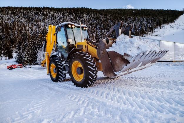 Spychacz czyszczenia śniegu na górze. czyszczenie drogi dla samochodu.