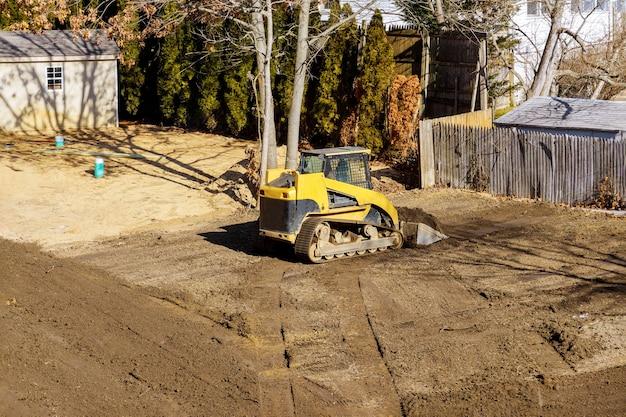 Spychacz w ruchu, wyrównanie terenu na placu budowy w ziemi za pomocą łopat