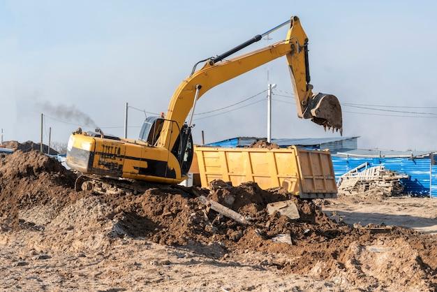Spycharka koparka kopiąca ziemię, odgarniająca plac budowy