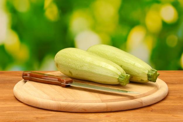 Squash na desce do krojenia na drewnianym stole na zielono