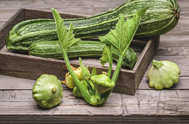 Squash w drewnianym pudełku, pattypan squash na drewnianej powierzchni, zielone liście warzyw.