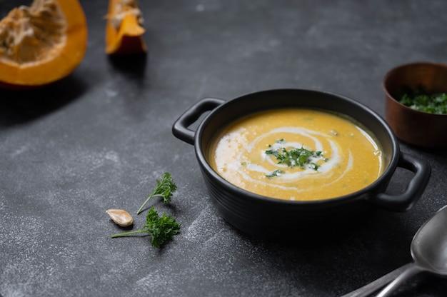 Squash wegańska zupa, kremowa jesienna zupa w czarnej misce na ciemnym tle. jesienne potrawy.