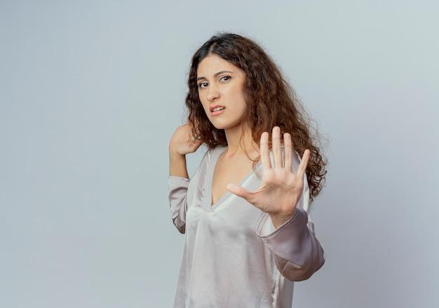 Squeamish młody ładny żeński pracownik biurowy pokazuje gest zatrzymania na białym tle na białej ścianie
