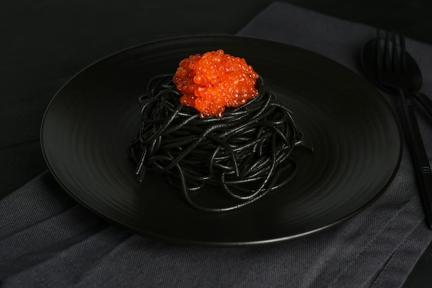 Squid atrament czarny makaron z czerwonym kawiorem w czarnym talerzu na ciemnym tle. czarne spaghetti z owocami morza.