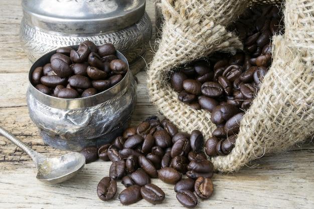 Srebna filiżanka i kawowe fasole w parcianej torbie na drewnianym tle