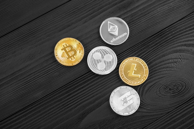 Srebne i złote monety z bitcoin, czochrą i eterum symbolem na drewnianym tle.