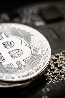 Srebny bitcoin na tle płyty głównej komputera
