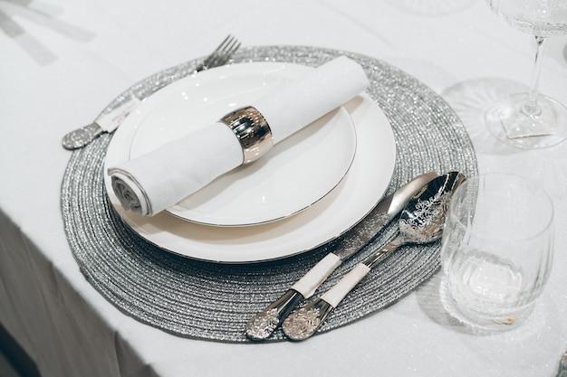 Srebny bożenarodzeniowy stołowy położenie na bielu stole