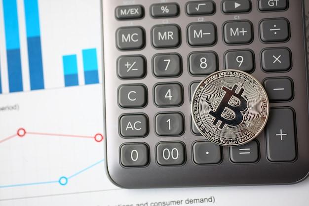 Srebny btc znaka monety lying on the beach przy statystyki wykresu zbliżeniem