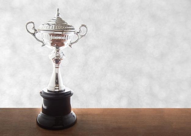 Srebny trofeum na drewnianym stole nad abstact bokeh białym tłem. zwycięskie nagrody z miejsca na kopię.