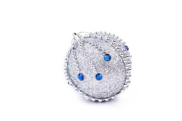 Srebrna brokatowa bombka z niebieskimi kamieniami.