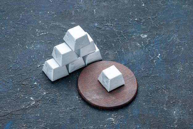 Srebrna czekolada utworzona na białym tle na ciemnym biurku