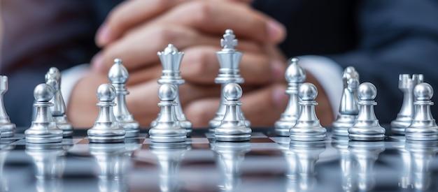 Srebrna drużyna figurowa w szachach (król, królowa, goniec, skoczek, wieża i pionek) z doświadczeniem menedżera biznesmena.