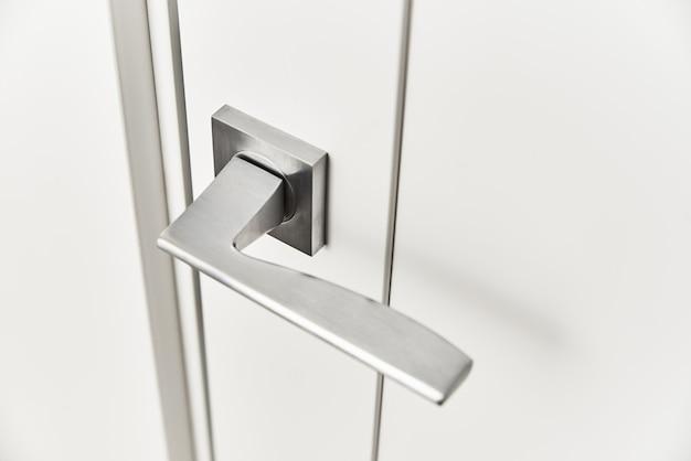 Srebrna klamka na białych drzwiach. akcesoria meblowe, element wnętrza