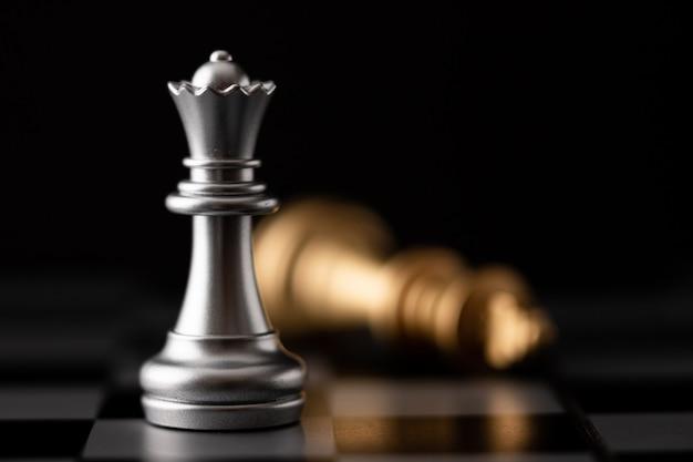 Srebrna królowa stoi i spada złoty król