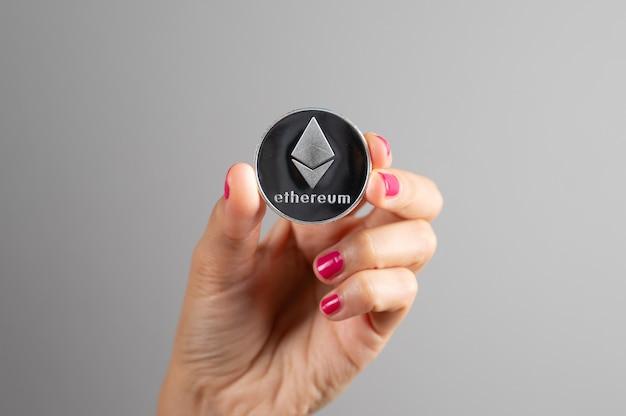 Srebrna moneta ethereum w kobiecej dłoni na szarym tle. kryptowaluta blockchain. wirtualna waluta money.crypto.