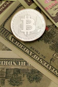 Srebrna moneta z krypto waluty znak i symbol na kupie banknotów dolara. pomysł na blockchain, nowy rodzaj pieniądza w gospodarce świata biznesu.