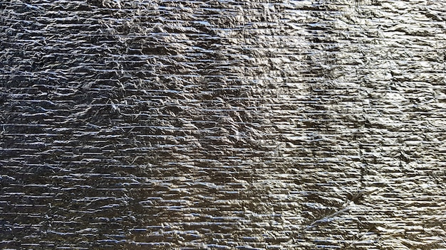 Srebrna szorstka pomarszczona tekstura folii. zmięty błyszczący tekstury folii metalowej lub tła dla projektu. cienki arkusz srebrnego liścia w tle z błyszczącą pogniecioną nierówną powierzchnią.