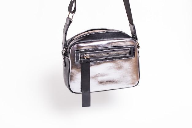 Srebrna torebka damska z czarnymi akcentami na białej ścianie