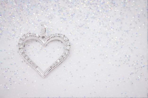 Srebrna zawieszka w kształcie serca na błyszczącym tle cekinów