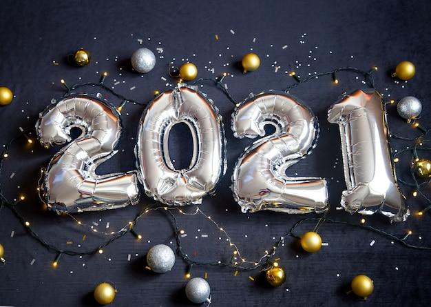 Srebrne balony foliowe wykonane numer nowy rok na czarnym tle z girlandą i kulkami.