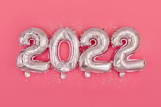 Srebrne balony foliowe z cyframi i konfetti płasko leżące