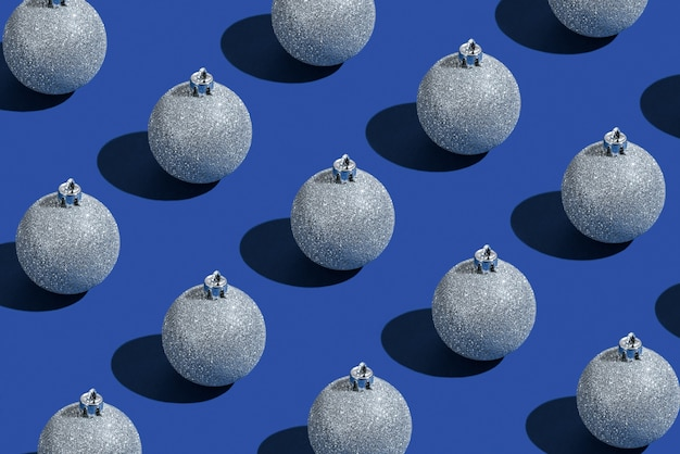 Srebrne bombki na niebieskim tle. karta noworoczna. minimalistyczny styl. kompozycja świąteczna. leżał na płasko, widok z góry, miejsce na kopię.