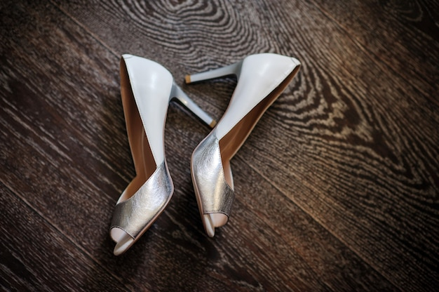 Srebrne buty panny młodej na drewnianej podłodze. dzień dobry koncepcja.