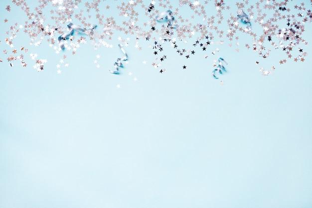 Srebrne cekiny w kształcie gwiazdy i srebrne wstążki na niebieskim tle. skopiuj miejsce