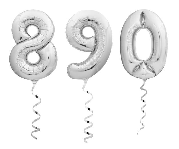 Srebrne chromowane cyfry 8, 9, 0 wykonane z nadmuchiwanych balonów ze wstążkami na białym tle