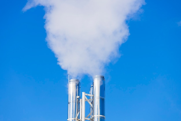 Srebrne fajki, z których kłębi się dym. pracująca kotłownia. zdjęcie wysokiej jakości