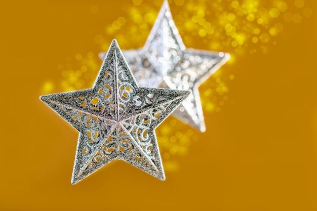 Srebrne gwiazdki świąteczne na złotym tle rozmytych świateł