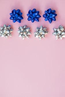 Srebrne i niebieskie łuki na niebiesko. kokarda świąteczna kokardka na prezenty dekoracyjne. srebrna wstążka z muszką z pustą przestrzenią na tekst pocztówka.