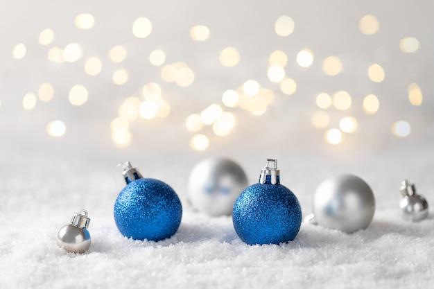 Srebrne i niebieskie ozdoby świąteczne na rozmytych światłach