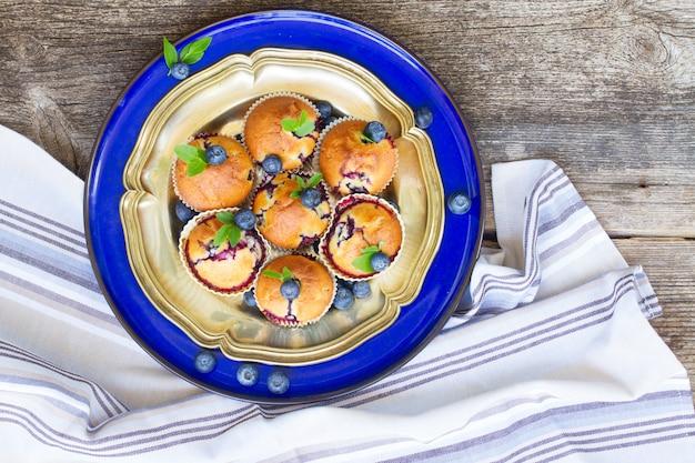 Srebrne i niebieskie talerze pieczonych babeczek z jagodami na stole