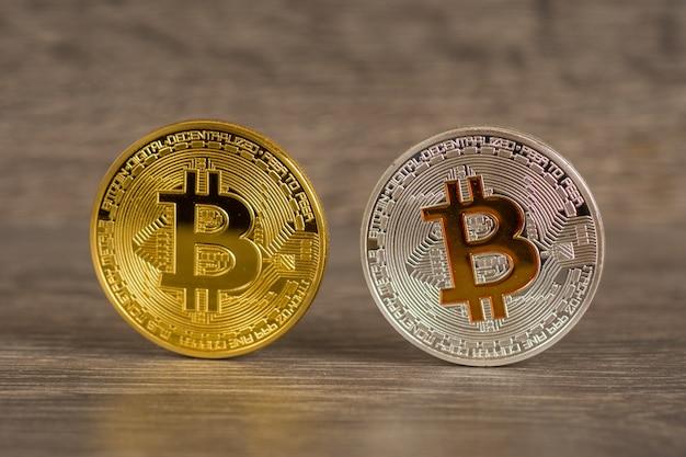 Srebrne i złote monety metaliczne bitcoin na drewnianym stole